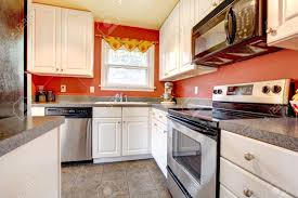 small kitchen room with concrete tile floor red walls steel