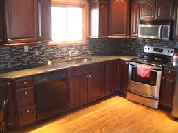 dark kitchen cabinets with black appliances grey ceramic tile