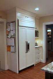 small cabinet on side of refrigerator with microwave in upper