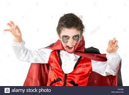 boy with face paint and vampire halloween costume isolated in