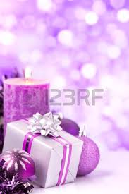 purple and silver baubles a gift and a candle in front