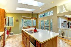 large green country kitchen with skylights and wood cabinets