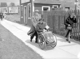 king george vi a man pushing a woman in a wheelchair to see king george vi and