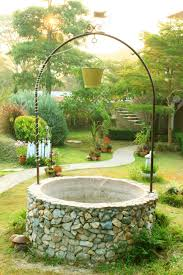 old well with a bucket in beautiful garden stock photo picture