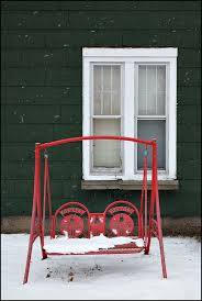 coca cola porch swing in front of an old house in a snowstorm