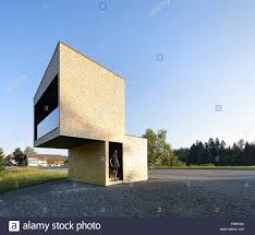 side elevation of cubic structure with man waiting bus stop