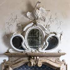 ornamental mirror above the fireplace of a venetian villa stock