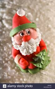 marzipan santa claus sat on top of iced christmas cake he has a