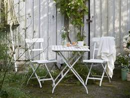 small patio table with two chairs a garden with a white small foldable table and two chairs all in