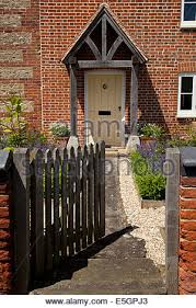 front gate and porch of pretty english cottage stock photo