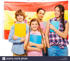 four happy students standing with spanish flag stock photo