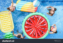 happy friends playing ball inside swimming stock photo 670239541