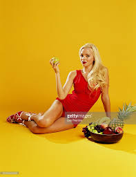 young woman in red bathing suit sitting by bowl of fruits stock
