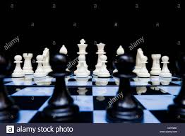 white chess pieces in set up position viewed from back line of