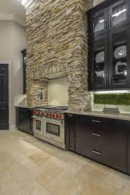 stacked stone is used to create a stunning rustic range hood above
