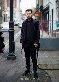 men s street style layered look with a black knit under a mac and