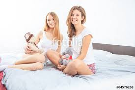 Girls In Bed by Two Girls In Bed Eating Cereal And Laughing