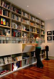 floor to ceiling white bookshelves and floorboards library