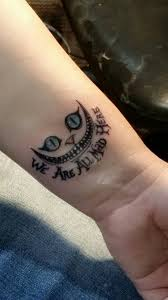 small cheshire cat smile with script wrist tattoo amazing tattoo