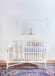 modern baby nursery with white crib and patterned area rug also