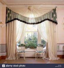sheer white full curtains with green trimmed pelmet with rosette