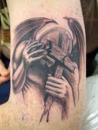 winged angel holding cross tattoo tattoos book 65 000 tattoos