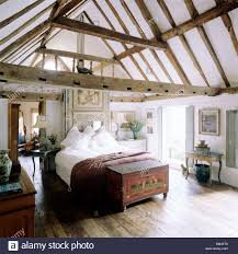 country bedroom with pitched ceiling and beams with wooden floor