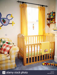 Yellow Curtains Nursery Baby S Wooden Cot In Front Of Window With Yellow Curtains In