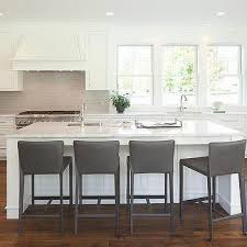 white and gray kitchen with gray leather counter stools and