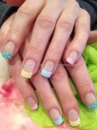 multi coloured pastel tips with white stripe and polka dot nail