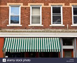 White Awning Storefront With Green And White Striped Awning And Apartment