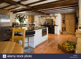 contemporary kitchen island unit with aga cooker and ceiling beams