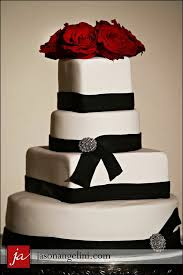 white fondant wedding cake with black ribbon and red roses
