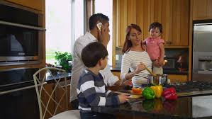 parents prepare food as children play in kitchen on r3d stock