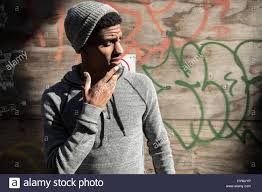a portrait of a young hipster posing infront of a wall of graffiti