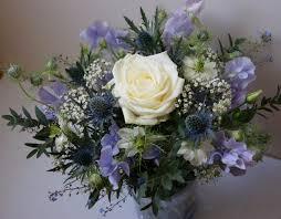 composition florale avec des roses bouquet champêtre baptême ou mariage blanc bleu rose chardons