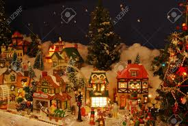 a miniature christmas village is all lit up people
