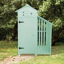 garden tool shed with log wood storage in sage green