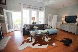 decorating farmhouse living room with wood flooring plus cow hide