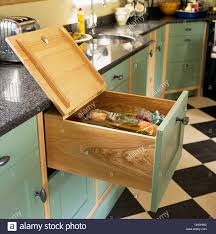 bread storage drawer with open lid in handmade pale green cabinets