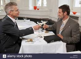 martini glasses clinking two men clinking glasses of martini in a restaurant stock photo