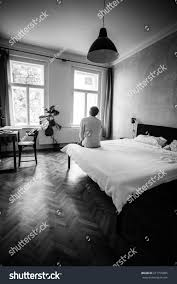young man sitting sad on bed stock photo 217755085 shutterstock young man sitting sad on the bed in the bedroom and looking from the window