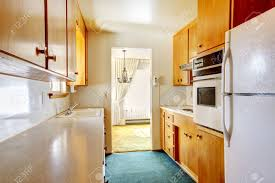 small kitchen room with blue carpet floor white appliances and