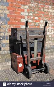 traditional old luggage trunks on a trolley on the railway