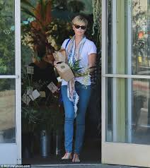 a casual looking charlize theron picks up some flowers from garden