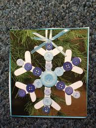 a cute snowflake ornament made with buttons and popsicle sticks