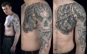 biomechanical skulls tattoo on biceps