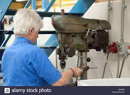 woman using a drilling machine pillar drill drill press in a
