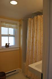 bahtroom white window plus small drapery and artistic artwork near