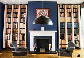 awesome library design in a warm reading room with black armchair
